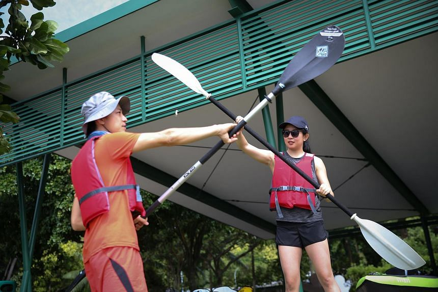 Journalist Clara Lock (right) getting some tips ahead of her kayaking expedition from Mr Clarence Chua, the founder of Ninja Kayakers.