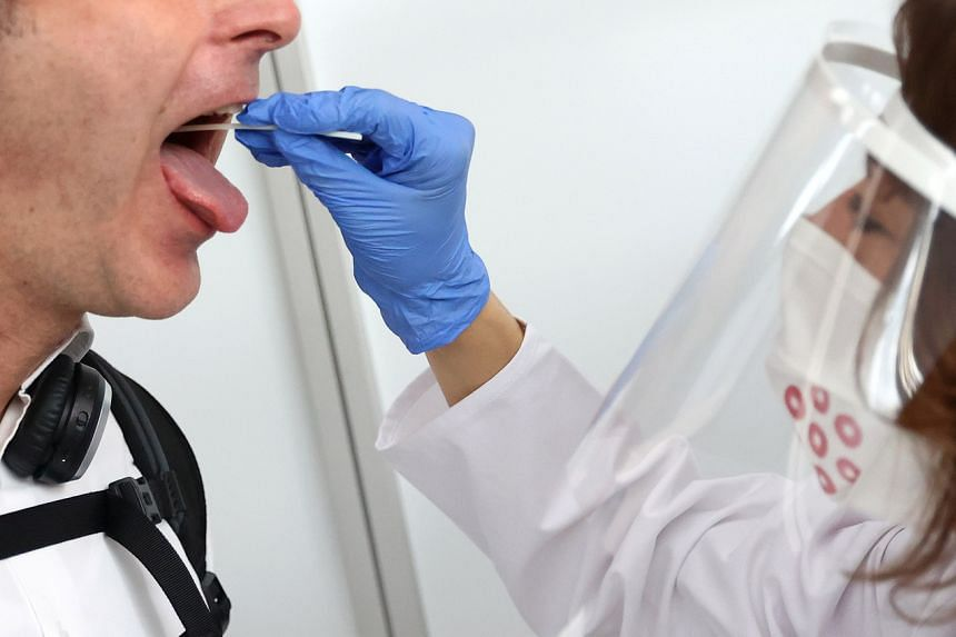 A healthcare worker taking a saliva sample at a walk-through coronavirus test centre in Frankfurt, Germany, on June 29, 2020.