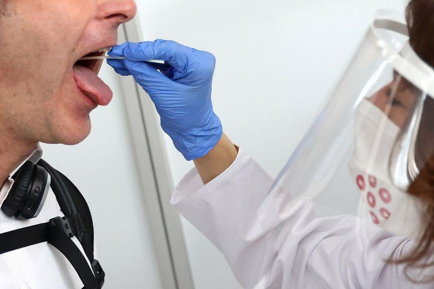 A healthcare worker taking a saliva sample at a walk-through coronavirus test centre in Frankfurt, Germany, on June 29, 2020.