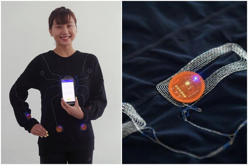 ST reporter Cheryl Tan tries on the smart suit, demonstrating how the LEDs light up when powered by the mobile phone.