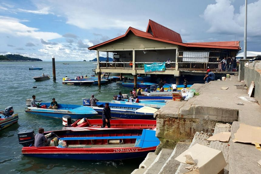 Boats awaiting passengers at the waterfront near Kota Kinabalu's markets, among them the Filipino Market, so named for the migrant traders and workers that abound there.