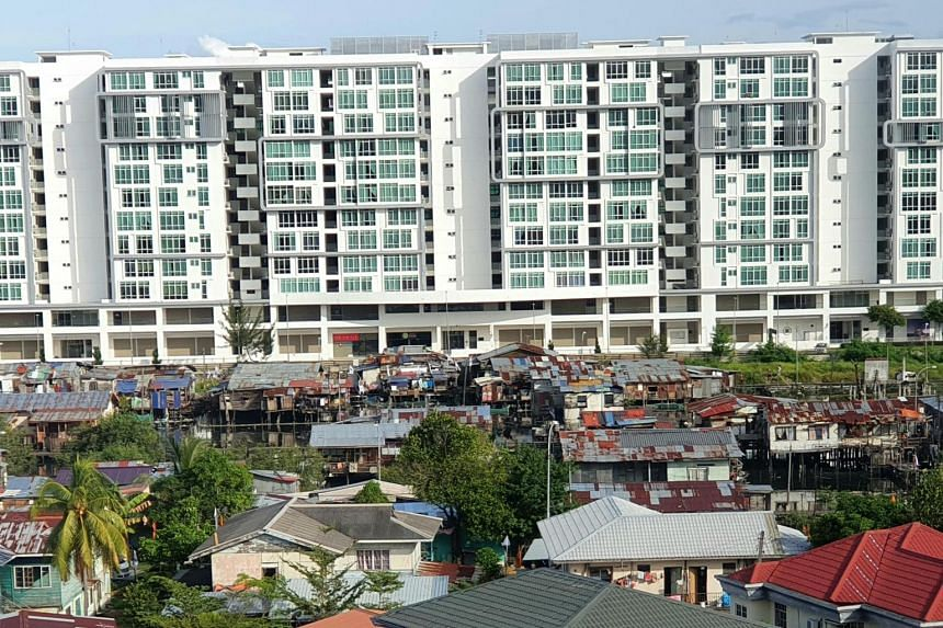 Squatters nestled between new developments are a common sight in Kota Kinabalu, where locals complain that illicit migrants are squeezing them out of the market.