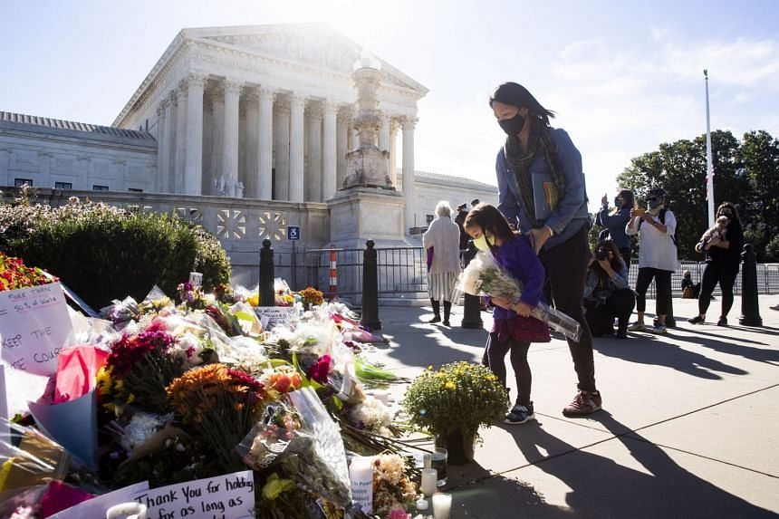 A child places flowers outside the Supreme Court in Washington.