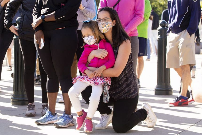 A child is held by a woman as people gather outside the Supreme Court to pay their respects.