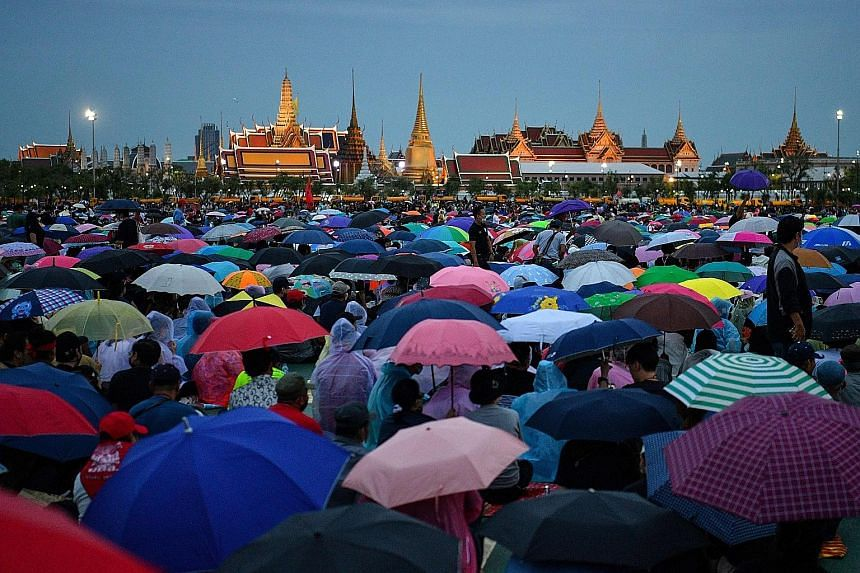 Protesters gathering yesterday in the rain in Sanam Luang, a field next to the Grand Palace, during a pro-democracy rally in Bangkok. PHOTO: AGENCE FRANCE-PRESSE