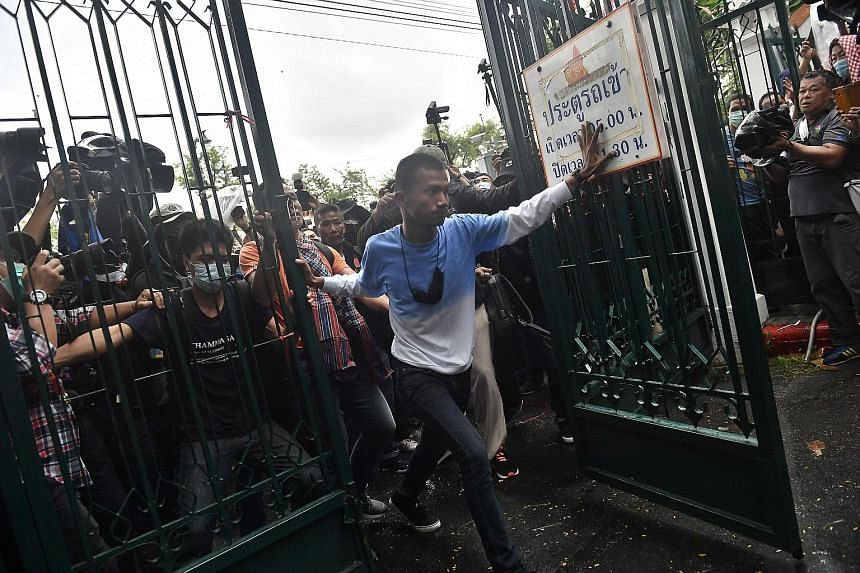 Above: Anti-government protesters, led by activist Panupong Jadnok (centre), breaking through a gate at Thammasat University in Bangkok yesterday. Left: Student Union of Thailand spokesman Panusaya Sithijirawattanakul (centre) speaking via a loudspea