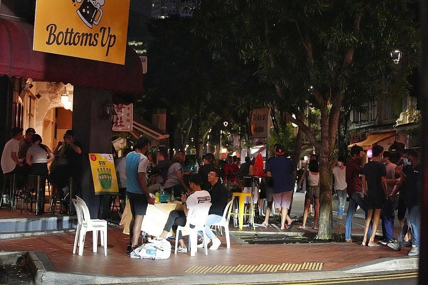 Patrons outside Bottoms Up on Friday. The Sunday Times understands that the bar in Telok Ayer Street was issued a fine earlier this month for not complying with safe management measures. With the Government clamping down on food and beverage outlets