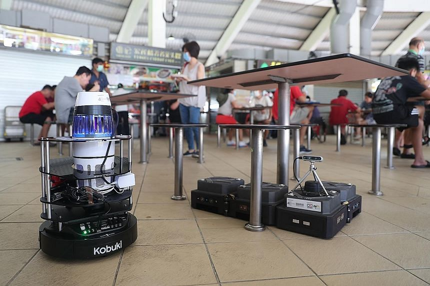 The robots being test-bedded at Tampines Round Market and Food Centre perform tasks like mapping the density of mosquitoes in the surroundings (left) and cleaning the floor.