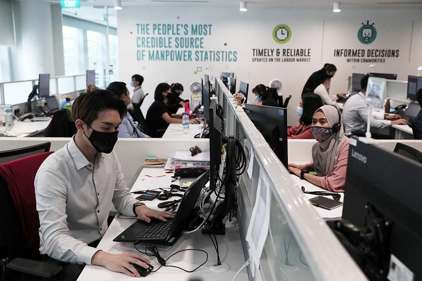 Customer experience officer Vincent Chen (left) and market research surveyor Nur Asfarina Mohd Ishak working at MOM's Manpower Research and Statistics Department.