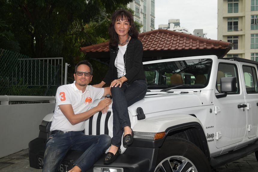 Manulife Investment Management Singapore chief executive Wendy Lim and her husband Gregory Trinh, an IT consultant, posing on a Jeep at their River Valley condo.