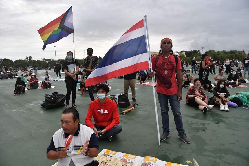 A pro-democracy protester holds a Thai national flag as another holds a pride flag on Sanam Luang field in Bangkok on Sept 20, 2020.