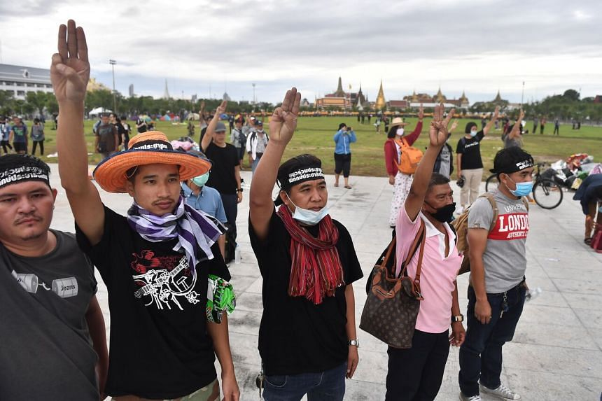Pro-democracy protesters hold up the three-finger salute on Sanam Luang next to the Grand Palace in Bangkok on Sept 20, 2020.