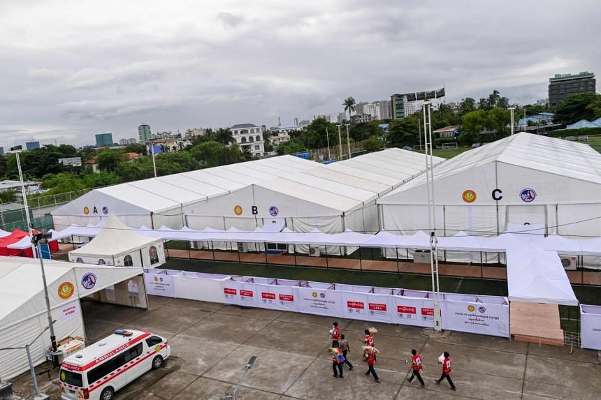 Myanmar red cross members work inside a temporary shelter for Covid-19 patients on a football pitch in Yangon on Sept 19, 2020.