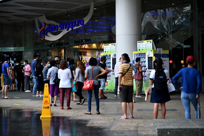 People queueing to collect their pre-ordered mask kits at Plaza Singapura on Sept 21, 2020.