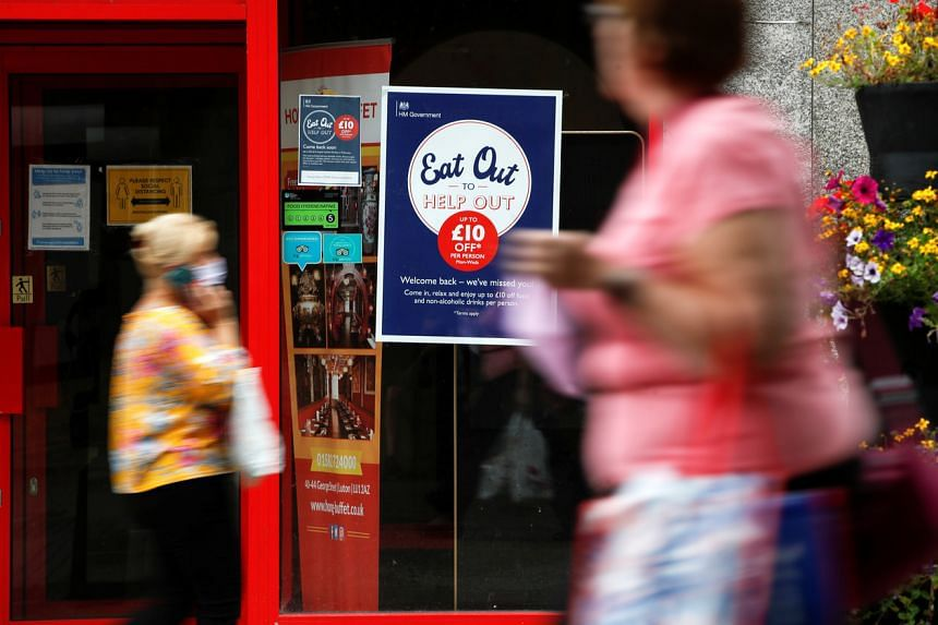 """People walk past a take-out restaurant with an """"Eat Out To Help Out"""" poster in Luton, England, on Aug 6, 2020."""