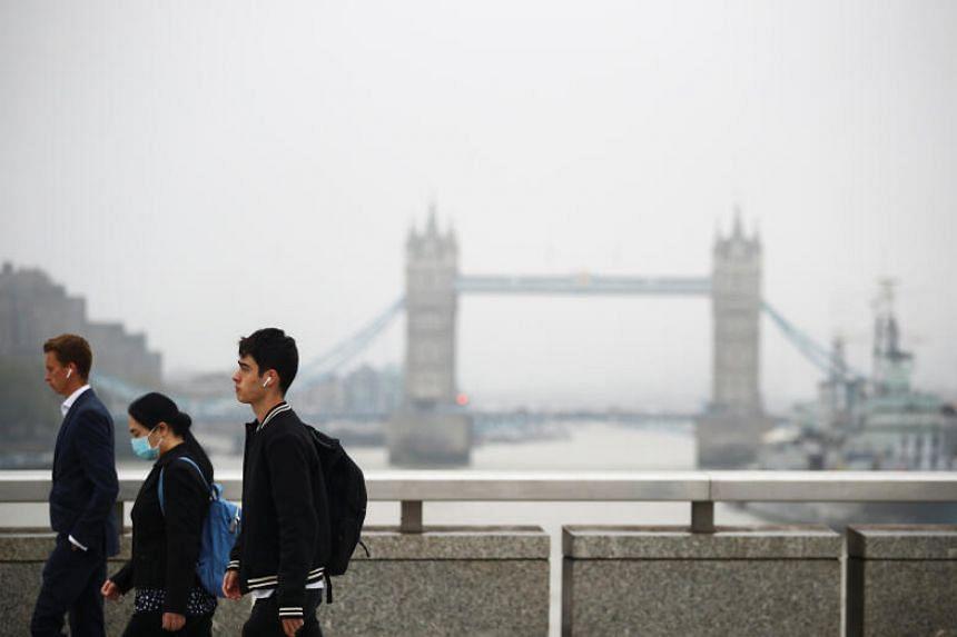 Commuters walk across the London Bridge in London on Sept 21, 2020.
