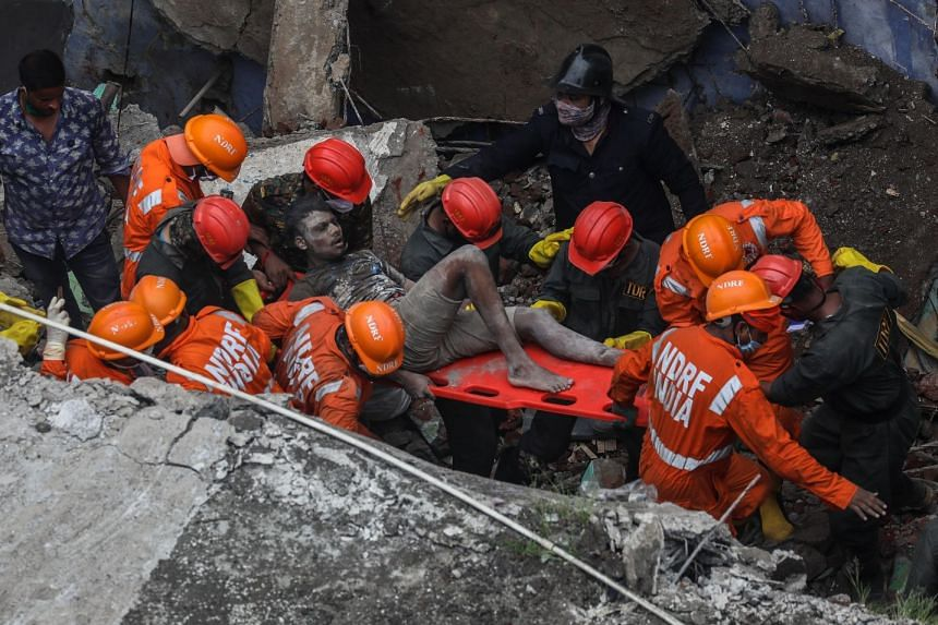 A survivor is rescued from the debris of the collapsed residential building on the outskirts of Mumbai, Sept 21, 2020.