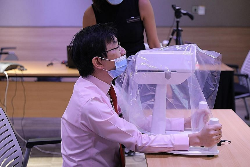 Dr Luke Tay, a consultant at SGH who was part of the team that developed the robot, demonstrating how a patient would position himself when undergoing a swab test done by the SwabBot.