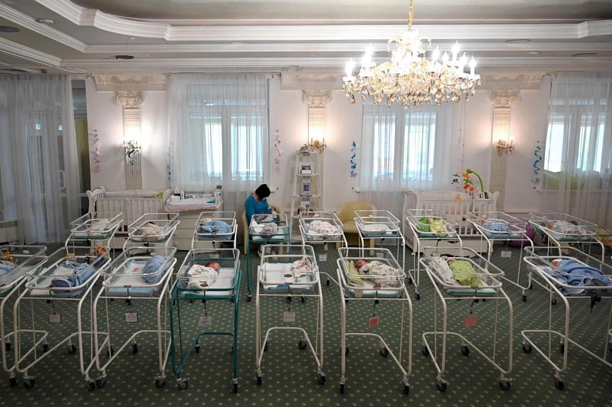 A nurse caring for newborn babies at Kiev's Venice hotel, some of the more than 100 babies born to surrogate mothers stranded in Ukraine on May 15, 2020.