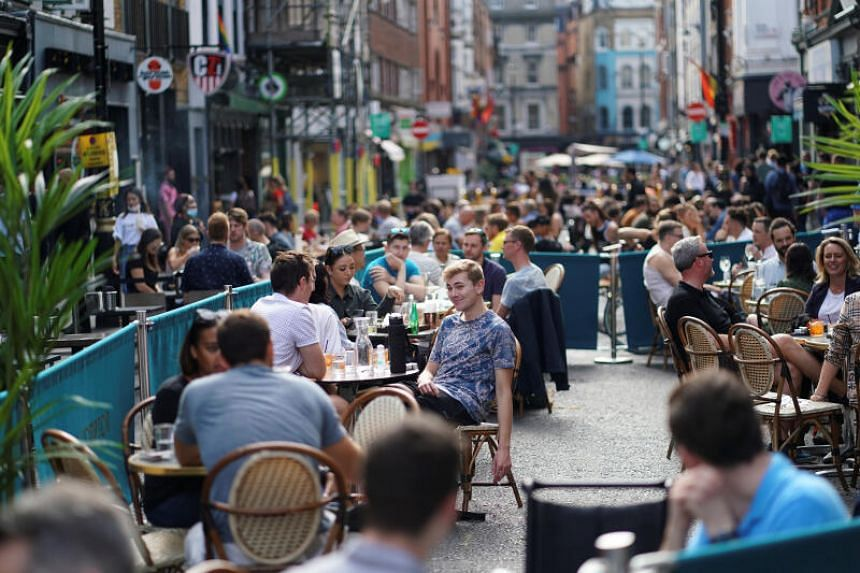 People sit at tables outside restaurants in London's Soho, on Sept 20, 2020.
