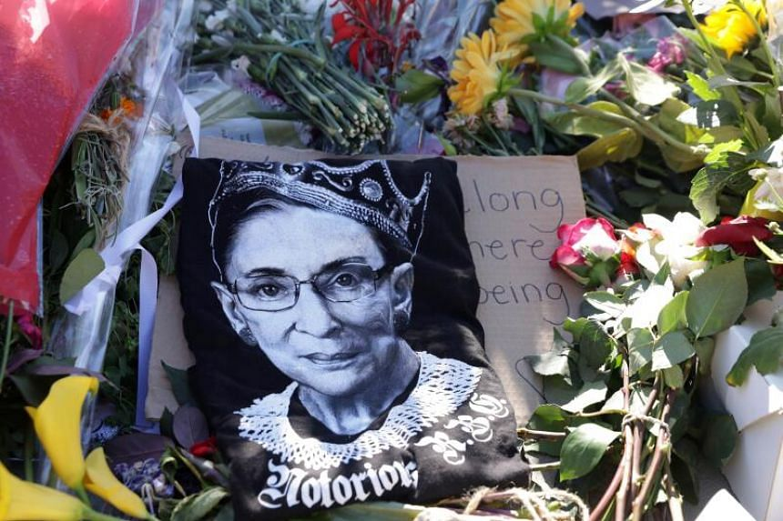 Signs and flowers are left at a makeshift memorial in front of the US Supreme Court for the late Justice Ruth Bader Ginsburg, in Washington DC, on Sept 21, 2020.