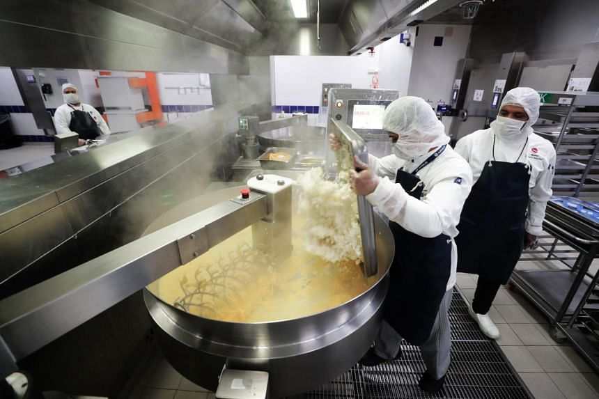 Workers preparing a large batch of food at a catering facility on July 19, 2019.