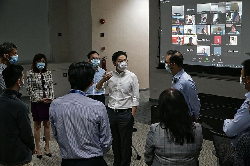 Education Minister Lawrence Wong speaking to IBM Singapore managing director Martin Chee at the company's premises in Changi Business Park yesterday. IBM's programme is part of a larger government effort by SkillsFuture Singapore to provide 30,000 tr