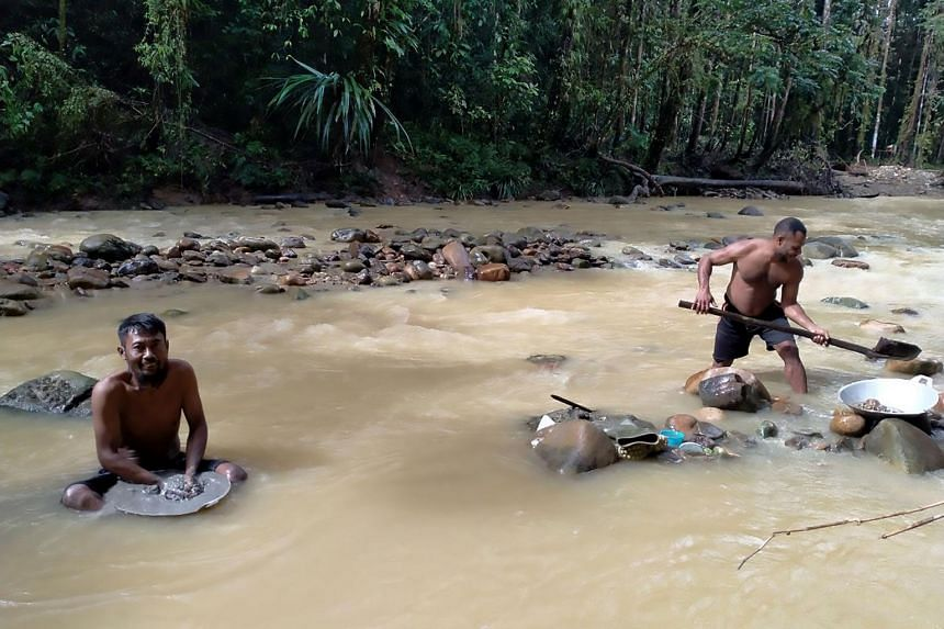 Two miners panning for gold along a stream near Korowai, in the Papua province.