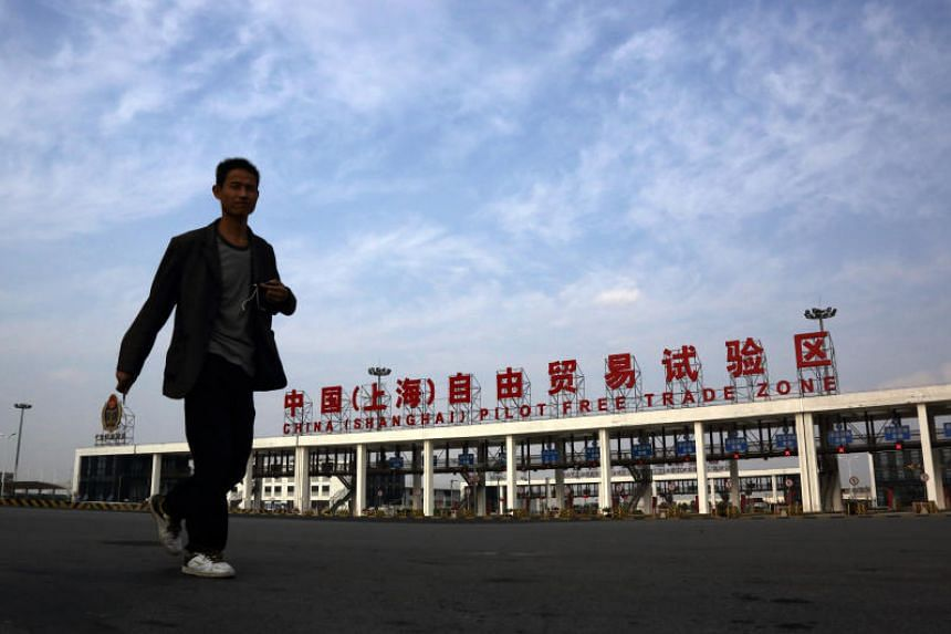 A man walks past the gate to China (Shanghai) Pilot Free Trade Zone's Pudong free trade zone in Shanghai, China, on Thursday, Oct. 24, 2013.