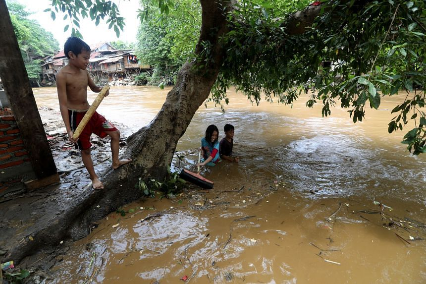 Left: A car swept away by floodwaters ending on top of debris in Pesawahan village in Sukabumi, West Java, yesterday. Below: Trash scrapers cleaning a dirty river (left) and children playing in it (right) yesterday after flash floods and landslides s