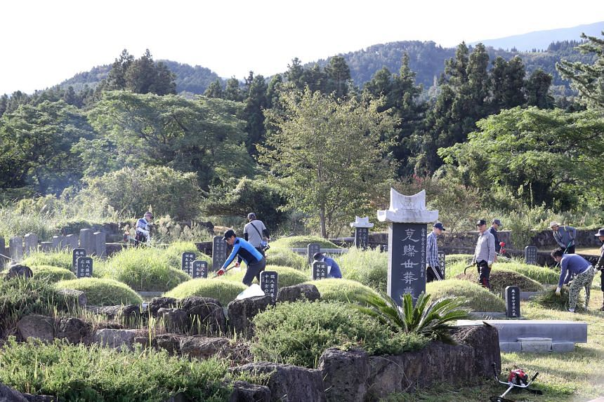 Visitors clearing the grass around their ancestors' graves on Jeju island, South Korea, last Sunday. On Monday, the government announced that all 11 national cemeteries will be closed from Sept 30 to Oct 4.