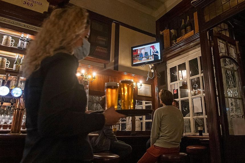Patrons at a London pub watching British Prime Minister Boris Johnson addressing the nation about the latest updates on the country's Covid-19 restrictions on Tuesday. The measures, starting today, entail an extension of the mandatory use of face mas