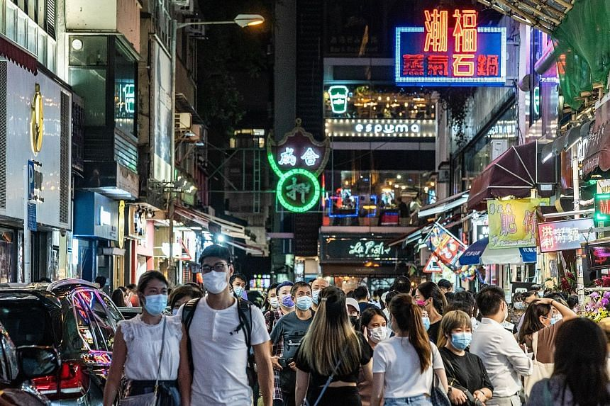 Above: People in face masks out and about in Hong Kong's Tsim Sha Tsui on Sept 11. The city has doubled the number of people allowed to gather in public, and reopened sports venues. Left: Shoppers at a mall in Hong Kong two Fridays ago. PHOTOS: BLOOM