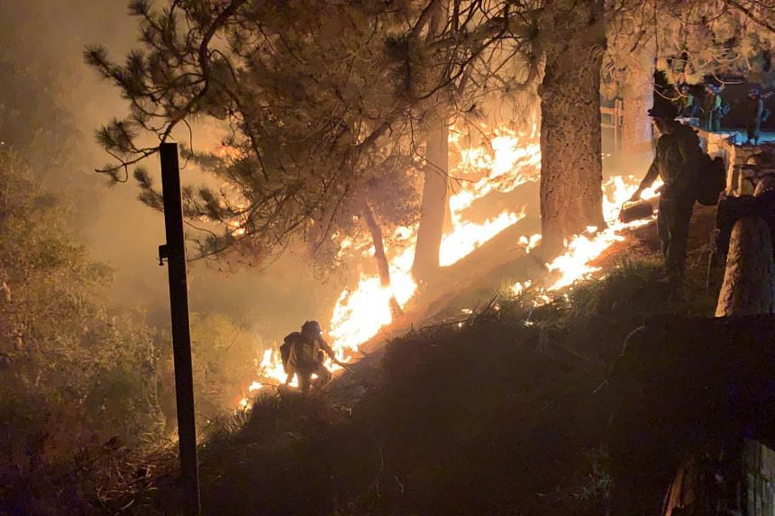 Firefighters try to extinguish the Bobcat Fire in Mount Wilson, California on Sept 23, 2020.