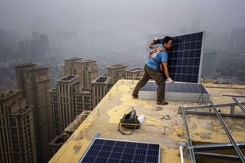 A 2018 photo shows a wroker installing solar panels atop a 47-storey high-rise in Wuhan, China.