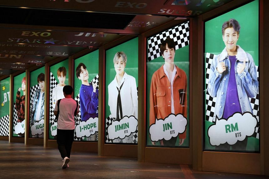 A man walks past commercial posters showing K-pop group BTS members outside a shop in Seoul.