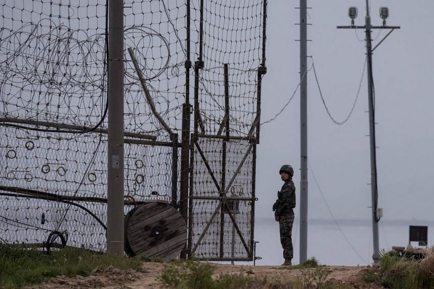 A photo from May 5, 2017, shows a soldier standing at the fence of the Demilitarised Zone near Ganghwa.