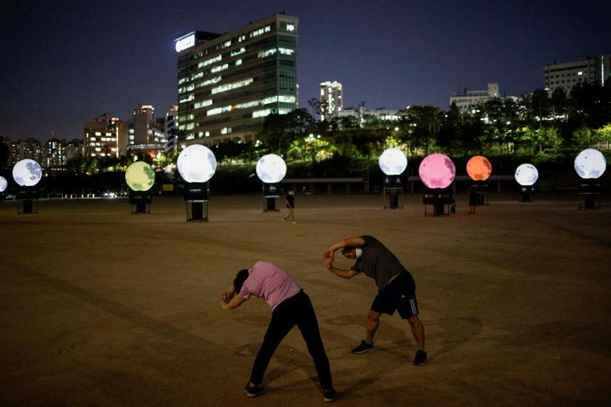People exercise next to artificial full moons to celebrate the upcoming Chuseok holiday in Seoul on Sept 21, 2020.