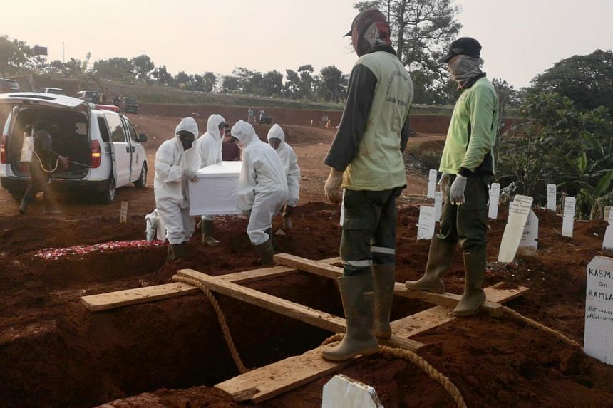 A body being moved into a grave as gravediggers watch on at the Pondok Ranggon public cemetery in East Jakarta.