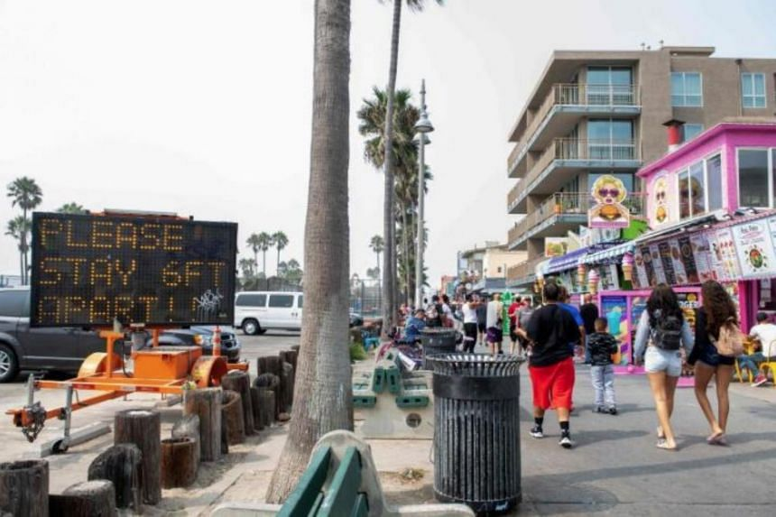 People walk past a sign on the boardwalk in Venice Beach, California, on Sept 15, 2020.