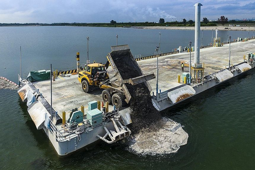 A dump truck discharging incineration ash from the Floating Platform at Semakau Landfill. A tugboat and barge berthed at Semakau Landfill.