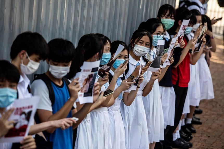 In a photo taken on June 12, 2020, school students hold signs during a pro-democracy protest near their school in Hong Kong.