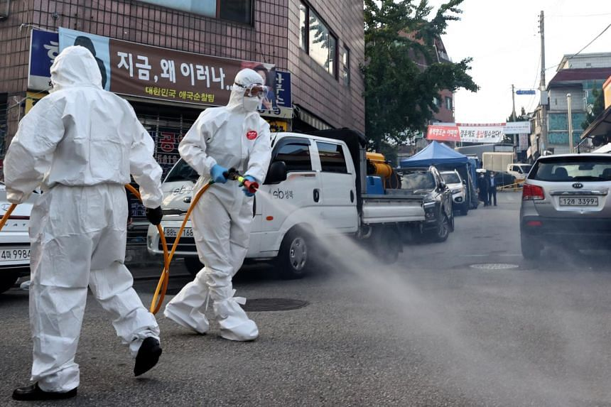 Health workers disinfect streets near Sarang Jeil Church in Seoul on Sept 24, 2020.