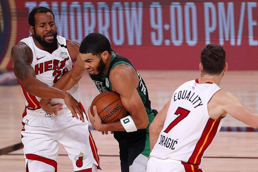 Boston Celtics' Jayson Tatum driving past two Miami Heat players during Game 5 of the Eastern Conference Finals. PHOTO: AGENCE FRANCE-PRESSE