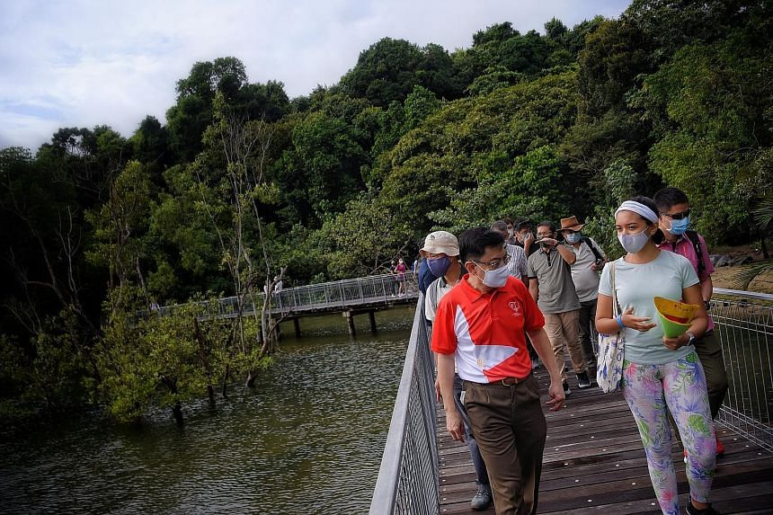 Deputy Prime Minister Heng Swee Keat (left) taking a tour of the Chek Jawa Wetlands with Naked Hermit Crabs lead volunteer Sumita Thiagarajan, 26, during a visit to Pulau Ubin yesterday. Mr Heng, who is an MP for East Coast GRC, said residents can al