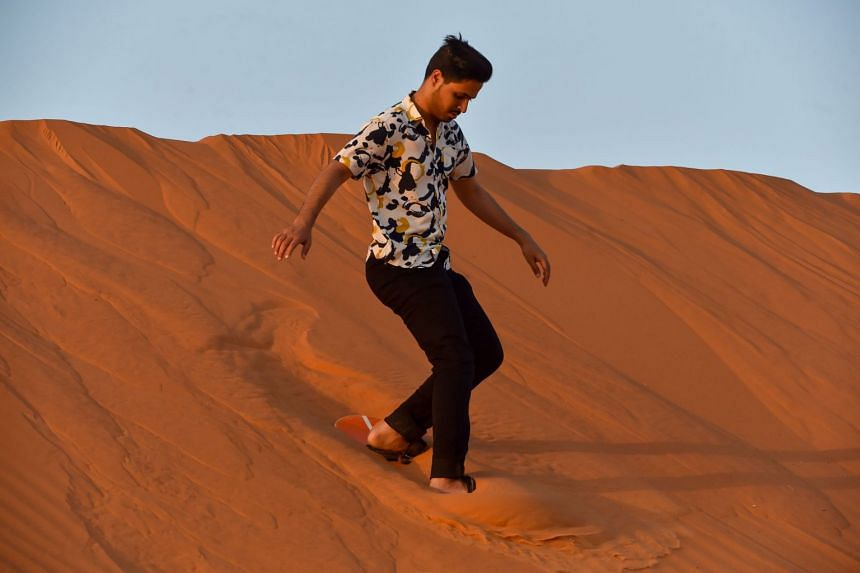 """A Saudi tourist surfs down a sand dune in the """"Saed"""" desert area, 110km eastern of Riyadh City, in August 2020."""