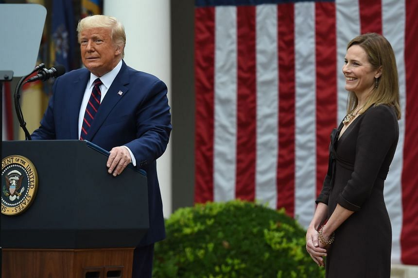 Trump announces his US Supreme Court nominee, Judge Amy Coney Barrett (right), in the Rose Garden of the White House.