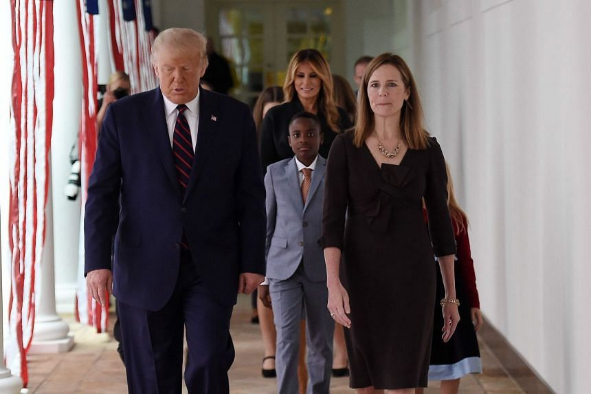 Trump (left) and Judge Amy Coney Barrett (second left), with US First Lady Melania Trump (centre rear), arrive at the Rose Garden of the White House.
