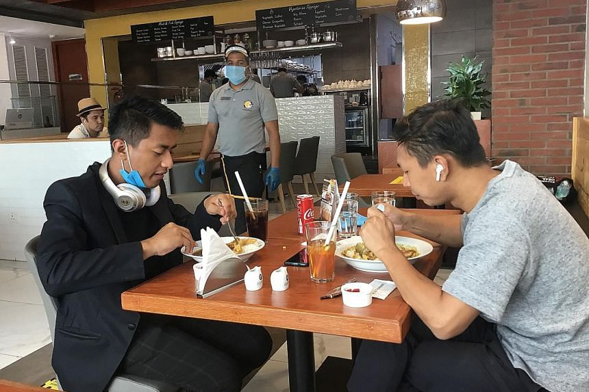From left: Business partners Rajikant Mangkhom and Lohit Chand Mangkhom eating at CoCo Ichibanya in Gurugram, a Delhi suburb. The restaurant opened in August and averaged around 58 orders a day that month. ST PHOTOS: DEBARSHI DASGUPTA Sushi and More