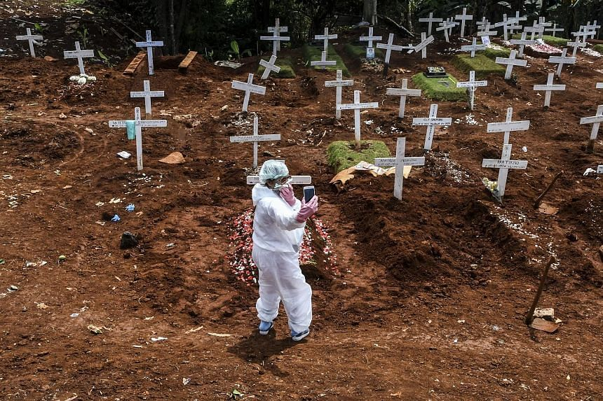 """Photojournalist Muhammad Adimaja wearing a custom stencilled face mask with words that loosely translate as """"virus protector"""". Right: A family member in a protective suit taking a picture at the grave of a Covid-19 victim in Pondok Rangon cemetery in"""